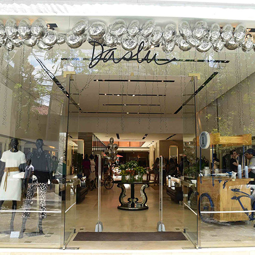 Facade all glazed in a sophisticated women's clothing store, all in light beige tones, marble floors and luxurious decor. At the front, to the left, two mannequins wear high-grade women's clothing.