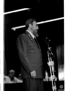 Black and white photo. Fidel Castro standing and sideways, in front of a microphone.