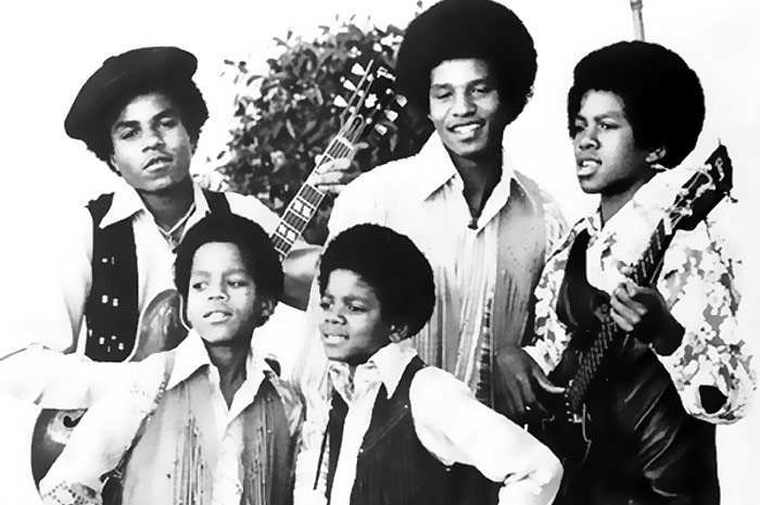Black and white photo of the Jackson Five Set. In the first plane, the 2 smaller brothers, one of them, Michael Jackson. Behind, the 3 bigger brothers, holding guitars.
