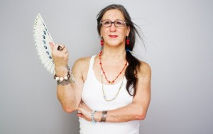 Color photo shows Laerte from the waist up, dressed as a woman, long hair with ponytail, red lipstick, white tank top, red necklaces and earrings, silver bangles and rings. One hand holds a white fan.
