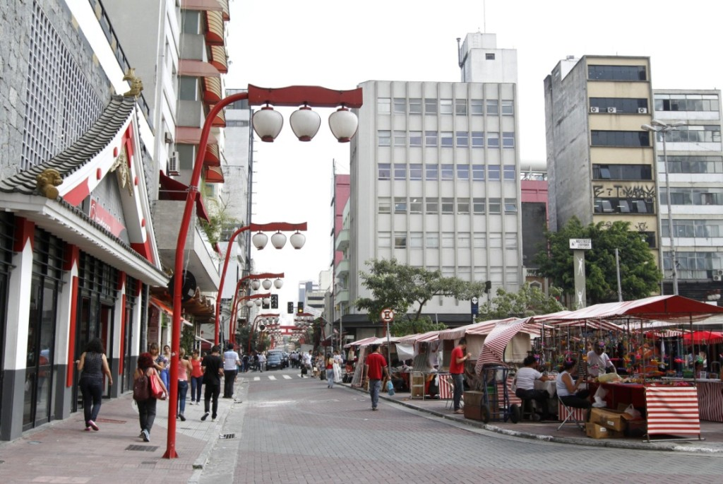 To the left, facade of building with Japanese architectural elements; Several people walking on an accessible sidewalk with several red lighting posts, which have 3 white lampshades in the form of Japanese lanterns. To the center, street turned into boardwalk. To the right, several colorful flower stalls and handicrafts. In the background, several buildings and some trees.