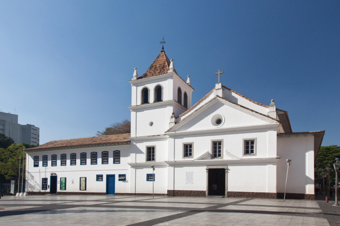 Facade all white, with reddish-brown roofs. On the left, a fairly large building with 2 floors; The lower one has 2 navy blue doors with small windows; On the top floor, 9 windows with navy blue border. In the center, tower with 4 floors; On the ground floor, small window with navy border; On the first floor, a window with a gray border; In the second, small round window; In the third and last, steeple with two large openings on each side; Above, pointed roof with architectural elements at the tips and a vane at the top. To the right, chapel with 3 floors; On the ground floor, large wooden door; In the first, 3 windows with gray border; At the last, a small round window and a cross at the top of the roof. Above and in the background, very blue sky without clouds.