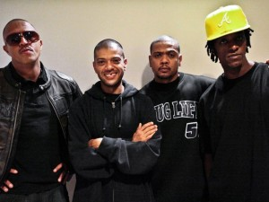 4 young black men wearing dark clothes. The last, on the right, wears a yellow cap.