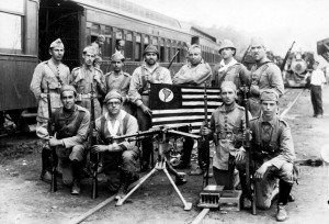 Black and white photo. In the first plane, four crouched soldiers holding rifles in one hand. Among them, a machine gun leaning on a tripod. Behind, 7 foot soldiers carry rifles on their backs. Everyone is on the rails of a train. In the background, on the left, train cars and to the right, farther away, a locomotive.