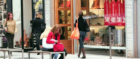 3 women carrying shopping bags walk down the sidewalk, watching the shop windows of several designer stores, one of them with several posters with discount promotions. A 4th woman sits on a bench, fiddling with her purse.