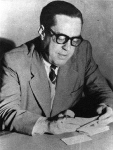 Black and white photo. Dark-haired man, from the waist up, wears thick-rimmed glasses and a light suit with black tie. He looks down at a document in his hands, both arms resting on a table.