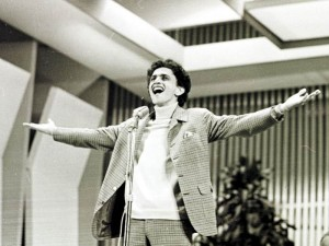 Black and white photo. A young Caetano Veloso sings with open arms, having a microphone in front of him.