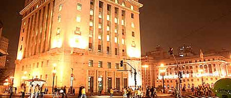 Night image of the facade and left side of a large square building with 13 floors, all lit by strong yellow lights. The 1st floor is very tall and has 5 large doors, side by side. All floors up have rows with 7 windows side by side. On the right, farther on, the side façade of another large building with rows of windows from end to end, also all lit by strong yellow lights. At the street level, a long sidewalk where several pedestrians cross.