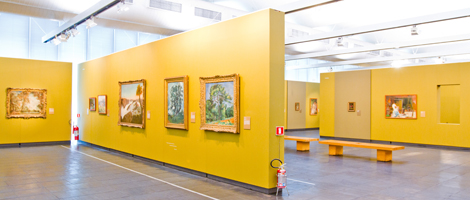 Inside gallery image. Local has several yellow murals approximately 8 meters long by 3 meters high, arranged against and perpendicularly to the windows, where several pictures are exposed.