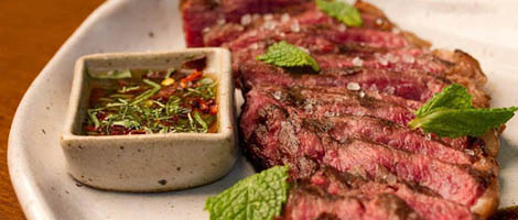 On a plate of tall, rounded edges, a large grilled steak barely past, all sliced into thin strips, with a few mint leaves. On her left side, a small square pot with herbal sauce.