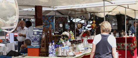 La mujer de espaldas de la cintura hacia arriba camina entre varias carpas con estructura tubular y techo de lona blanca, con objetos de arte y decoración como vasos, estatuillas, jarras, etc.