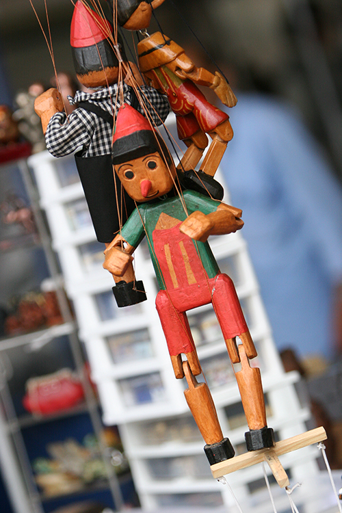 Close-up photo of 3 wooden marionettes with articulated arms and legs, all suspended by strings attached to arms and legs. The 1st is on the front, has a green and red clothes painted on the body. The 2nd is on his back and wears blue and white cloth clothes. The 3rd, further down, has a red dress painted on the body.