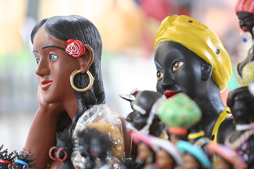 Close up photo shows 2 wooden dolls from the neck up. The 1st, on the left, represents a mulatto woman in profile, with straight black hair, a red rose attached to her ear and a large round earring. The 2nd, on the right, represents a black woman wearing a yellow turban and red lipstick.