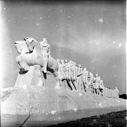 Black and white image. The monument has about 11 meters of total height by 9 meters of width and 44 meters of depth, all made in granite. From left to right, in the front, 2 men riding horses side by side. Behind them, there is a group of men pulling a canoe, which is also pushed from behind by a few more men.