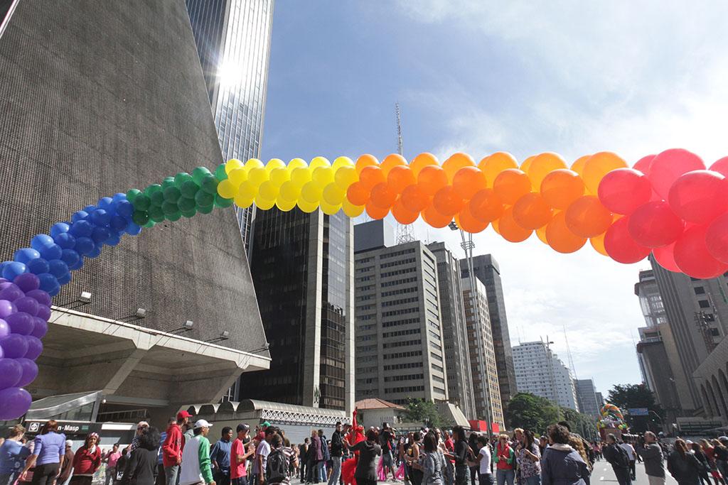 Avenida cercada por grandes prédios comerciais, totalmente ocupada por milhares de pessoas. Sobre elas, um grande arco feito com centenas de balões, em grupos de cores roxa, azul escuro, verde, amarelo, laranja e vermelho.