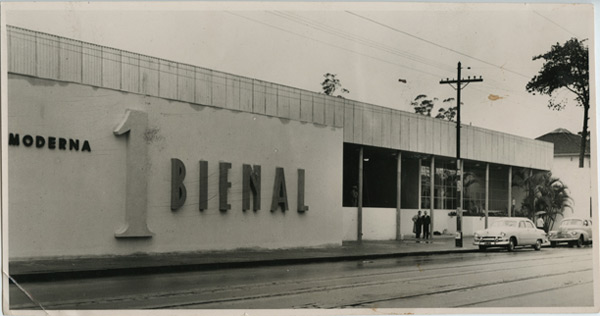 "Black and white image. Facade of a building with 1 floor all white and quite wide, occupying more than half a block. On the left side, with large letters in high relief, is written ""1st BIENNIAL""."