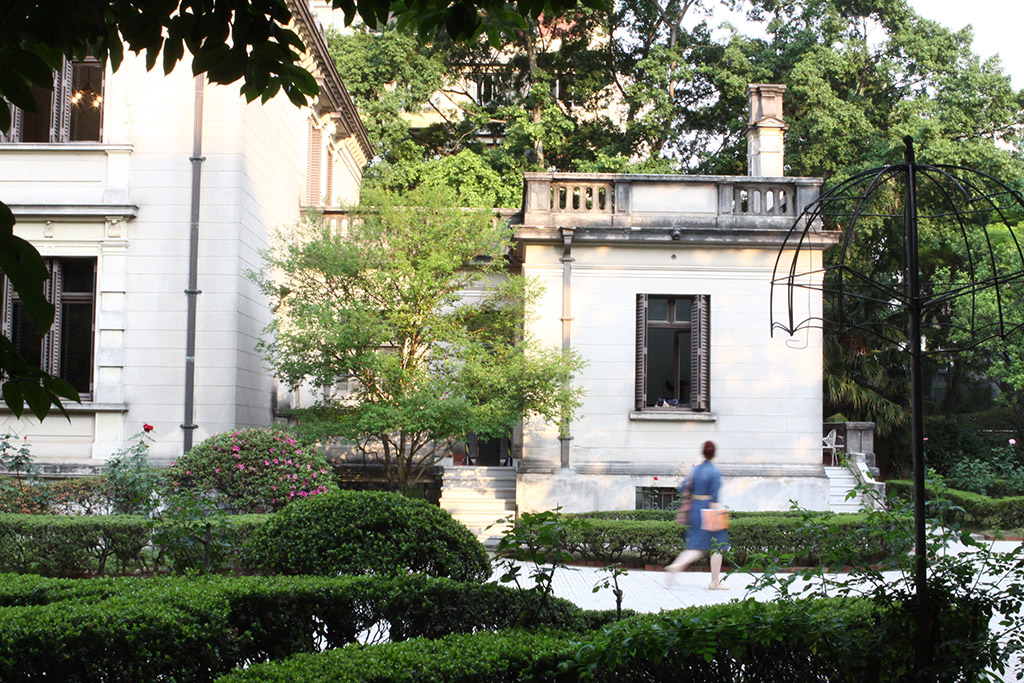 On the left side, part of the facade of a very light beige mansion with 2 floors, where a large window appears in each one. In the center, a small extension of the house with only one floor, a large window in the center and a terrace at the top. To the front, part of a large garden with shrubs and small trees, where a woman passes. In the background, another garden with several large trees.