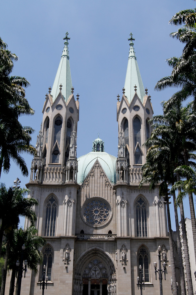 In the foreground, on both sides of the image, a row with very high imperial palms. In the center and in the background, cathedral neogothic style in shades of light gray. The facade, with a main portal and a large rose window, is flanked by two tall towers, both with a pointed ceiling, light green and very high.