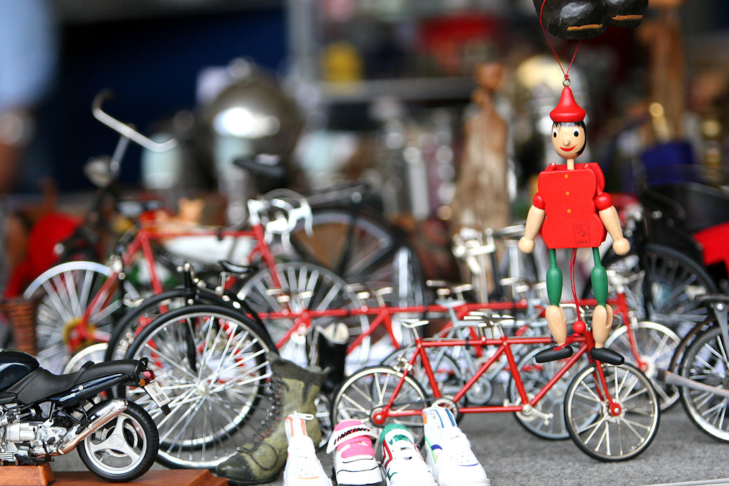 Closeup photo of a shelf full of miniatures of bicycles and motorcycles. On the right side, attached to the top, a small wooden puppet, with a red hat and blouse and green trousers.