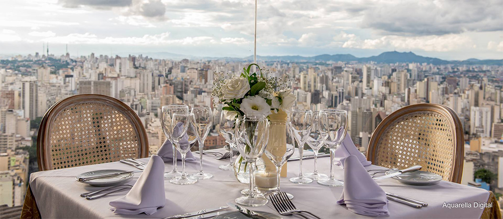 In the first plane, square table covered with towel and very clear blue napkins, silver cutlery, crystal bowls and a small vase with flowers in the center. On the sides, there are 2 light wooden chairs with braided straw back. Just behind, huge glass windows give panoramic views from the top of the city below with hundreds of buildings. Far away, a mountain chain, all under a cloudy sky.