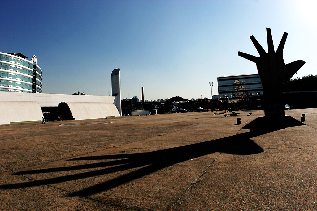 Over a large concrete-paneled area to the right stands a large one-hand sculpture with its fingers wide open, also in concrete, casting a long shadow over the floor on a sunny afternoon with very blue cloudless sky . In the far corner, in the left, two white one-storey buildings, quite long, with bold architectural forms, in tubular form.