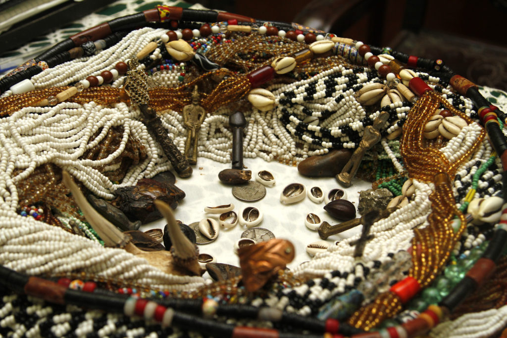Dozens of multicolored bead necklaces of various shapes and sizes, arranged on a white table in the shape of a square. In the center, some shells and coins.