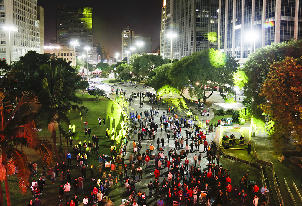 Night photo, from the top, from a huge, brightly lit square, between large commercial buildings. In the center, a wide, long alley full of people, lit by red lights. On both sides and along the whole way, extensive lawns with many trees of varied sizes.