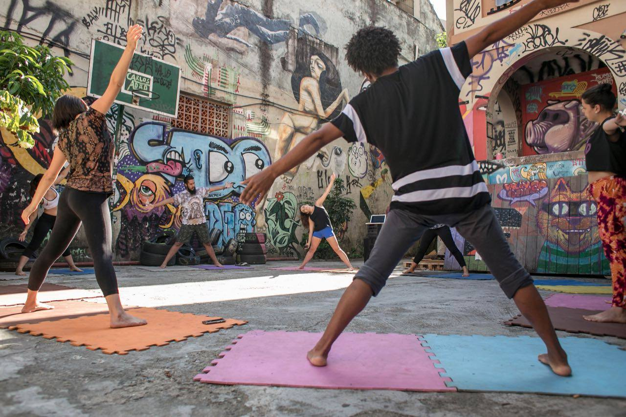 In an alley surrounded by walls full of multicolored graffiti, six people standing with arms and legs wide open, practice yoga on colored rubber mats.