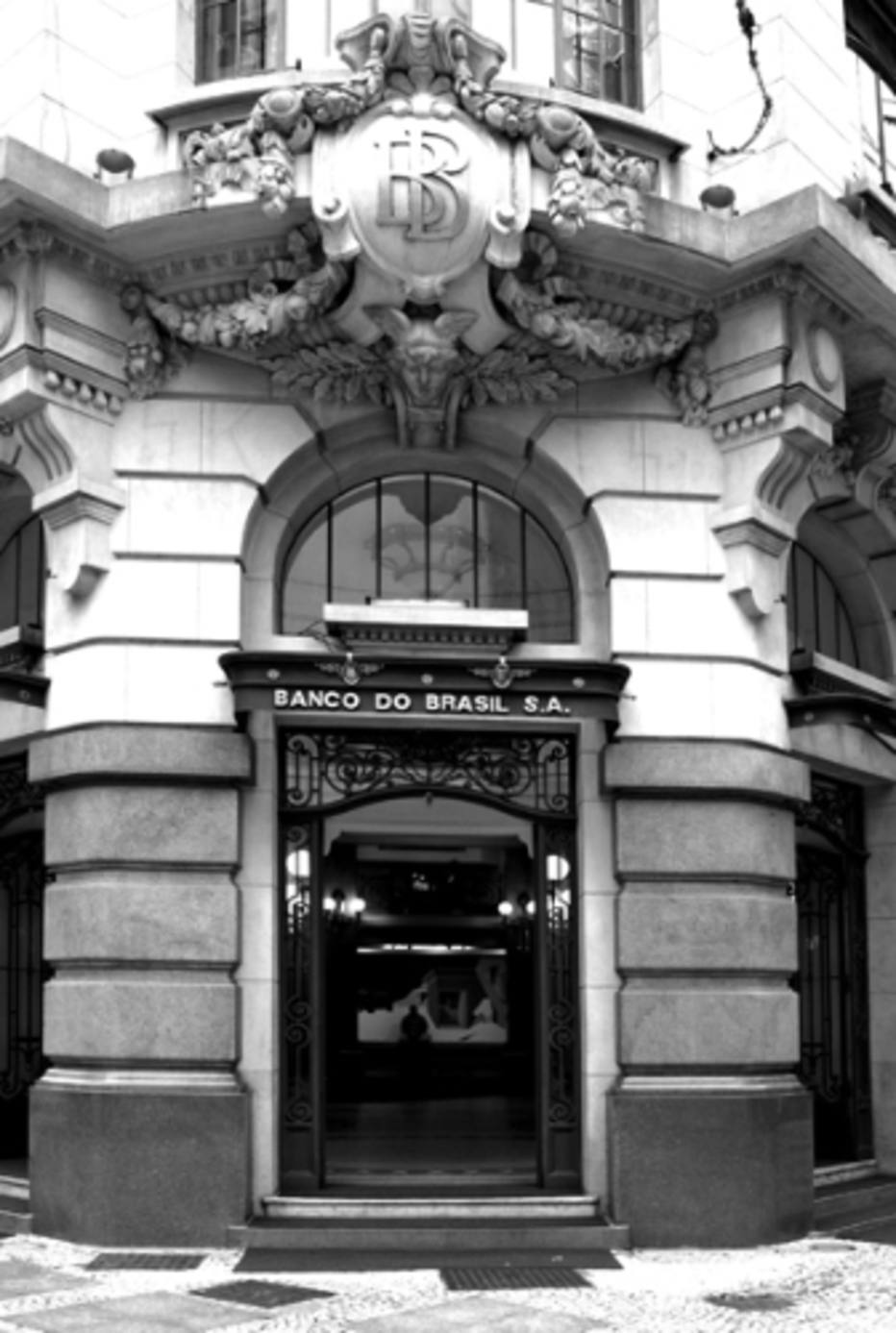 "Facade of the building in dark gray, light and white. In the center, a very wide and tall door with worked iron edges. At the top, sign with the words ""BANCO DO BRASIL S.A."". Above, a window with a rounded top. Between the 1st and 2nd floor, a type of concrete coat of arms on an eaves, all ornamented in the upper and lower part, brings in the center the letters ""BB"" superposed and in relief."