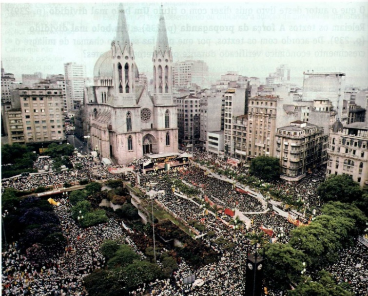 Aerial photo of Praça da Sé and surroundings, totally crowded by hundreds of thousands of demonstrators, who carry banner and posters. On the upper side of the square stands the grandiose cadetral of the Cathedral. On the right side are several commercial buildings, some of them very old.
