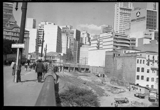 Black and white photo. To the right a construction site, a huge excavated area well below street level, where are some trucks and workers. To the left, sidewalk with some pedestrians. Dozens of buildings in the background.
