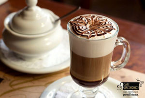 Image in close up. Cup of medium size, all glass transparent and full of coffee with milk. On the surface, on a thick clear foam, a stylized drawing made with fillets of light and dark chocolate. On the left side, a small sugar bowl all white.