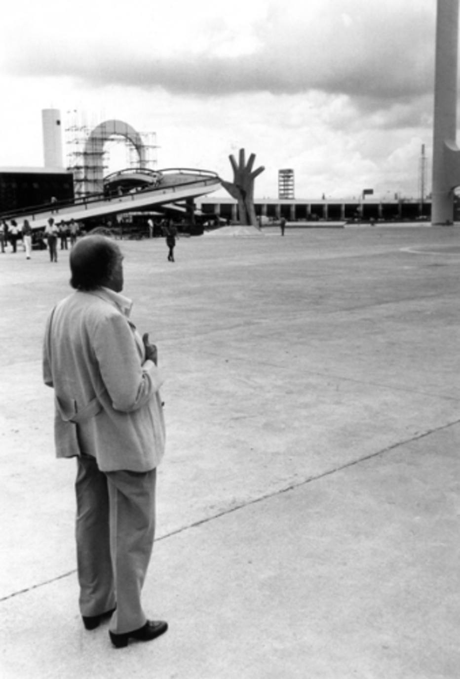 Black photo in white. In the first plane, image of the architect Oscar Niemeyer, of back, observing his work in the distance. To the bottom and to the left, a large curved walkway. In the center, the concrete sculpture of a huge open hand pointing to the sky, with the map of Latin America drawn on the palm and wrist. On the right, the first structures of the Memorial.