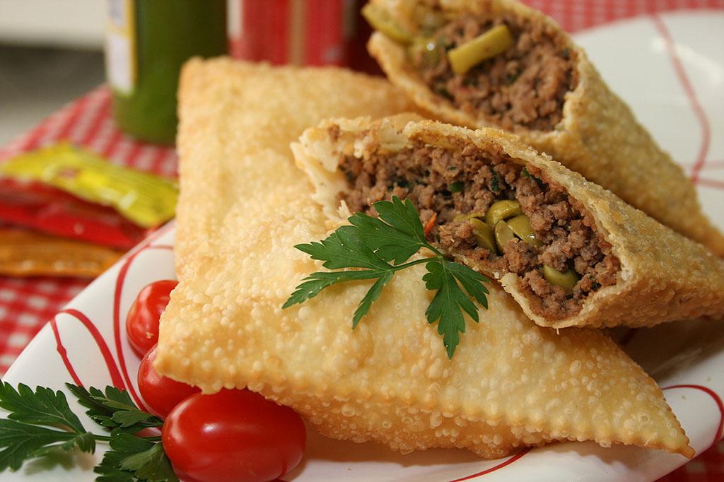 Sobre uma toalha xadrez vermelha e branca, um prato branco com 2 pastéis, 1 sobre o outro. O de cima está partido ao meio, expondo seu recheio de carne moída e azeitonas.
