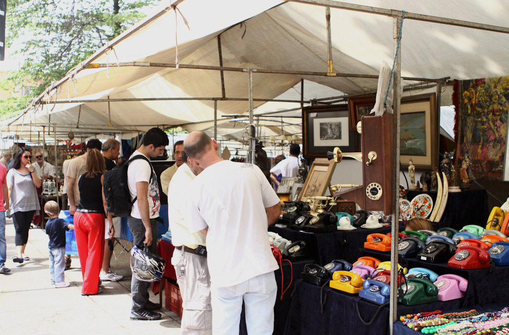 Several tents with tubular metallic structure and white canvas cover side by side, for sale of goods and antiques such as telephones, paintings, objects of decoration, etc. In front of the tents, several people watching and shopping.