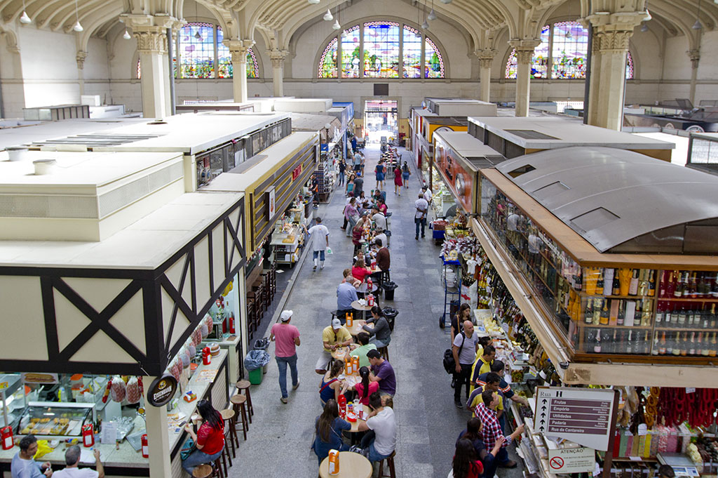 Photo from top to bottom of a large hall with very high ceiling. In the center, a very wide corridor from end to end with a row of small tables with benches in the center, all occupied by several people. On both sides, several stalls selling food, beverages, spices, etc. Further to the background, stand out 3 large beige light columns on each side, in Greek style. On the back wall is a very high and wide entrance door, and above, occupying the entire wall, three large multicolored stained glass windows in the shape of a semi-circle.