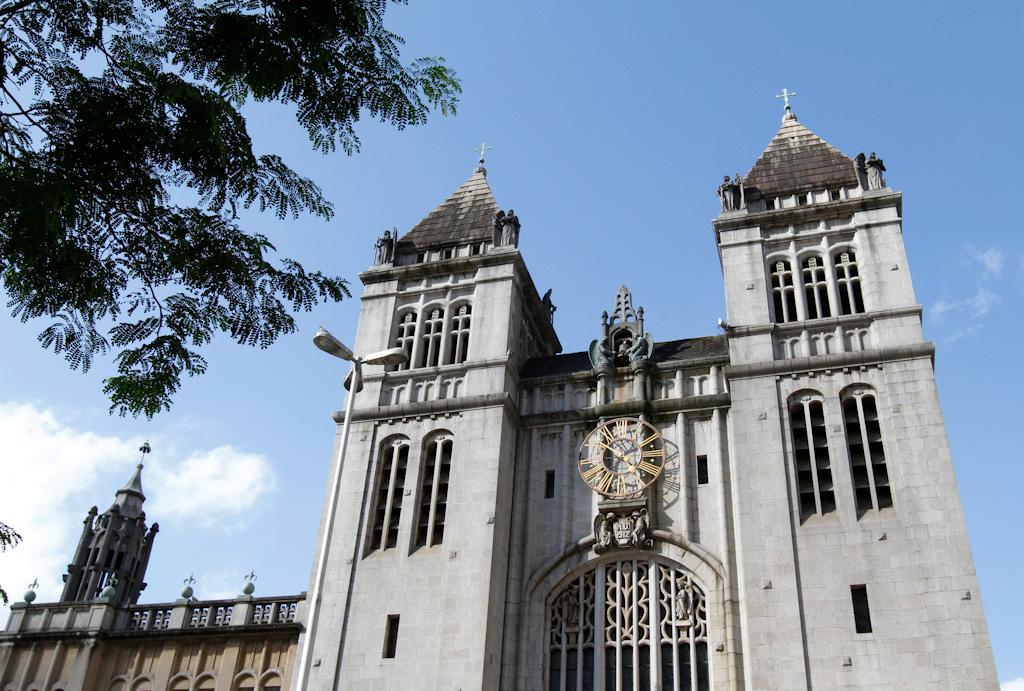 Imagem de baixo para cima. Fachada do Mosteiro em tons de cinza. Edificação bem alta, onde se destacam duas torres com vários janelões estreitos e compridos com o topo arredondado e telhados altos e pontiagudos, cada um possuindo uma cruz no topo. No centro, entre as torres, a edificação é mais baixa, possuindo um grande relógio no alto, feito por estruturas metálicas douradas. Acima, céu muito azul com poucas nuvens.