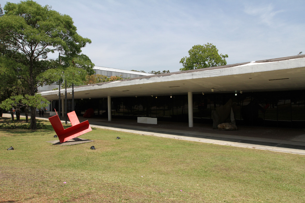 "To the right, facade of the museum, building with a floor and a large white slab of cover. The museum's entire wall of glazed, recessed metal structures provides a large free and covered area. Opposite, on the left side on a large lawn, a metal sculpture in red steel plates surrounded by lamps embedded in the grass, in the shape of two large opposing ""L"" letters. In the background, some trees. All under a blue sky with few clouds."