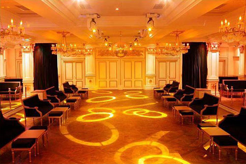 Large hall fully lit by powerful orange fixtures, attached to the ceiling, that project circles of light on the floor, where there are several black armchairs with light wood frame. Around it, still on the ceiling, several classic crystal chandeliers.
