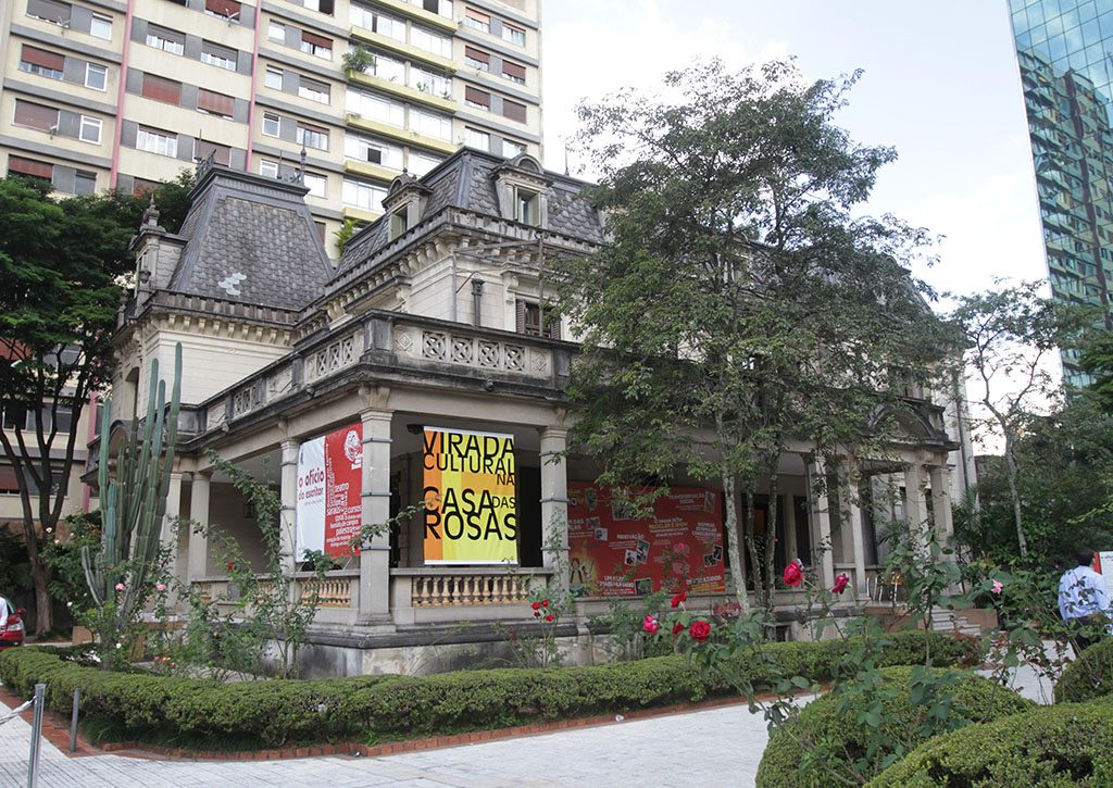 "Very old building with 2 floors, in shades of gray. On the first floor, a balcony surrounds the front and sides, covered by the slab of the terrace above, slab supported by several round columns. On the left side, a large yellow and orange poster is written in large black letters ""VIRADA CULTURAL"" and ""CASAS DAS ROSAS"". On the upper floor, large terrace with walled concrete wall surrounds the upper floor, smaller than the ground floor. Above, a very high roof of gray tiles with 4 windows of an attic. It is surrounded by a very flowery garden, shrubs and a few trees."