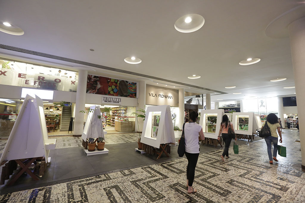 Internal image. It stands out very smooth and uniform floor, formed by small white Portuguese stones with designs of identical geometric forms, repeated by all the floor, in the black color. In the center, on a black rubber walkway, an exhibition of pictures placed on several triangular shaped wooden trestles covered by white cloth. In the background, several miscellaneous merchandise shops. The ceiling is all white, smooth, with several lamps embedded in a circle.
