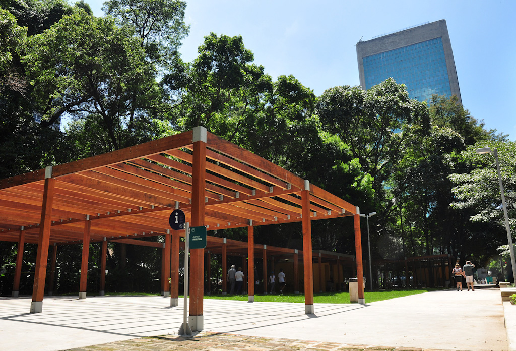 In a square with concrete floors and a dense forest with very tall trees in the background, stands a large structure all rectangular wood without walls. The ceiling is formed by a frame with a series of thin beams side by side, supported by several rectangular columns. Behind it all, the top of a tall commercial building of concrete and blue glass. Everything under a strong sun and a very blue sky without clouds.