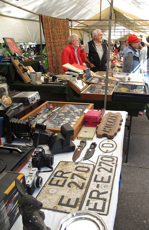 Tents with metal frame and roof in white canvas, side by side, exposes varied items of antiques such as car plates, cameras, medals, books, knives, among others. In the background, 3 men watch the goods.