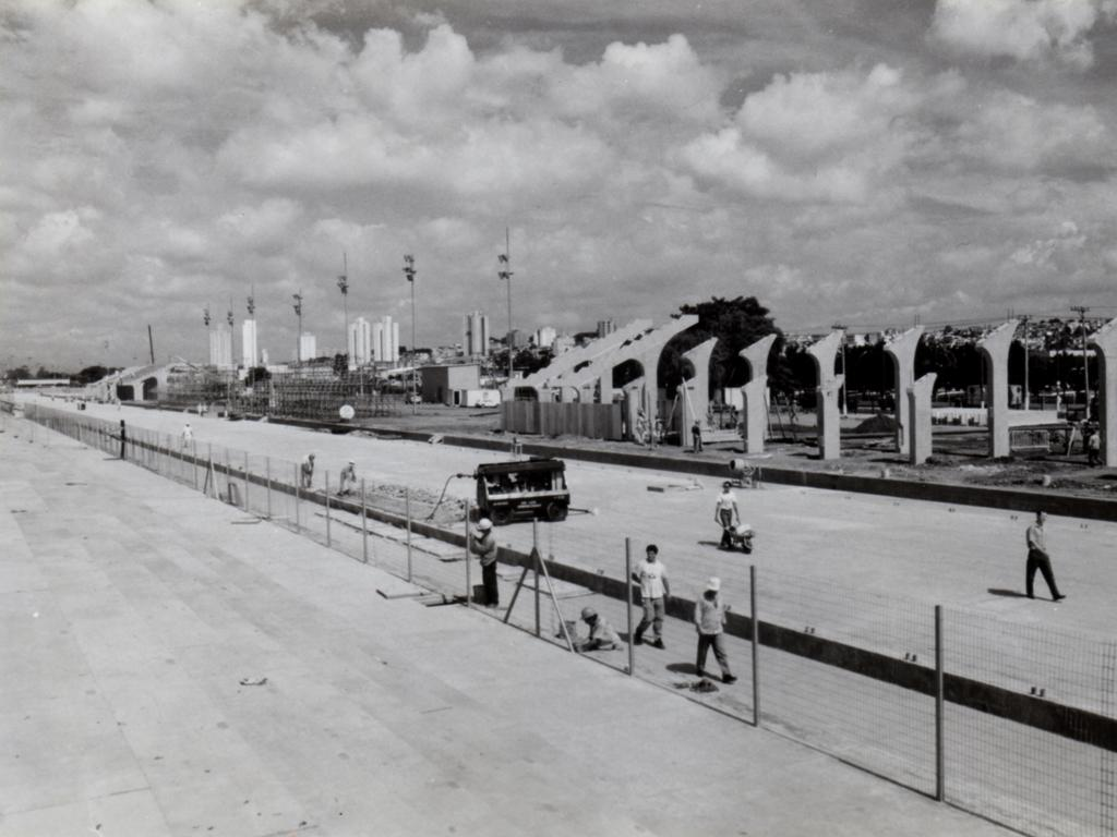 Black and white photo of construction site. In the first plan, workers are working on the construction of the future Samba Passarela. In the background, the first columns of the stands are erected, along the track.
