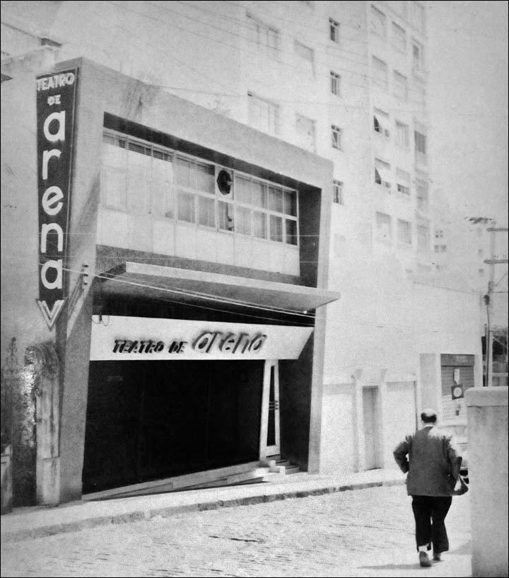 "Black and white photo, diagonal theater facade. Building of 2 floors in rectangular format. On the ground floor, entrance door with a large plaque at the top, with the words ""Arena Theater"". On the upper floor, large glass window with metal frame, from end to end. On the left side, at the level of the top floor, a large vertical plaque with the words ""Theater of"" in smaller letters and ""Arena"" in large letters. In front of the theater, to a street where a man walks."