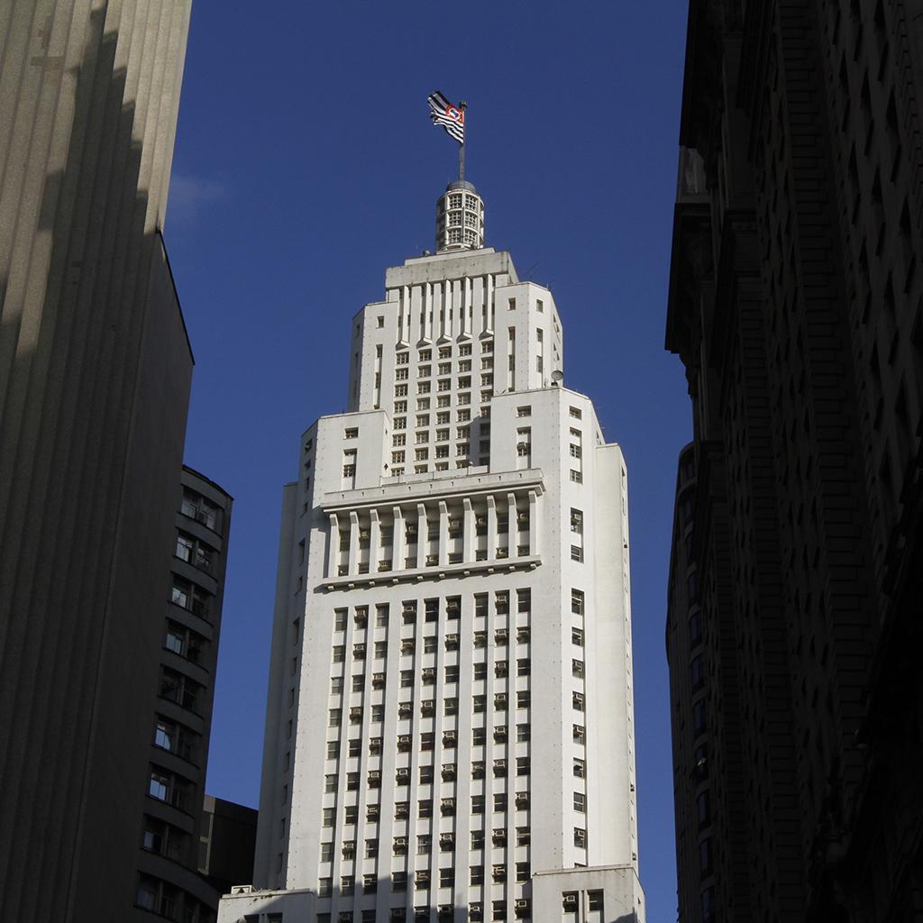 Edifício muito alto, todo branco, com centenas de janelas. Nos últimos 8 andares, a estrutura fica um pouco mais estreita. No topo, uma torre redonda de concreto e vidro com altura de 4 pisos e um mastro com a bandeira do Estado de São Paulo no topo. Tudo isso sob um céu muito azul e sem nuvens.