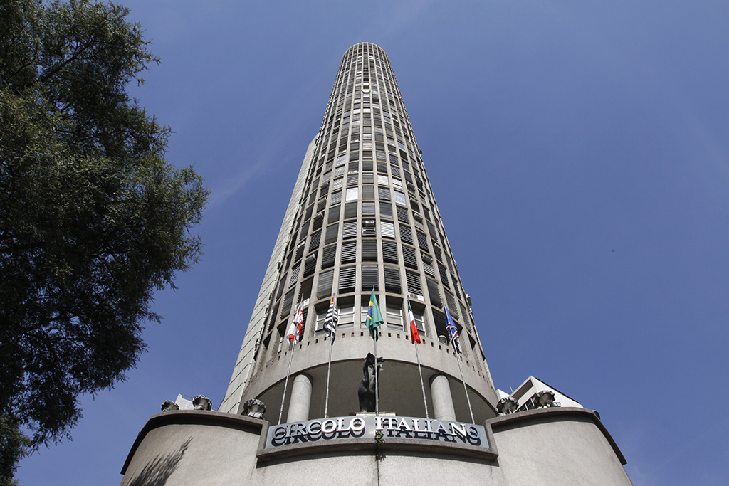 """Photo from below to a very tall oval shaped building with hundreds of windows with metal frame. On the 2nd floor there is a terrace and a large sign with metal letters attached to the wall of the building, with the words """"CIRCOLO ITALIANO"""". On the left side, part of the canopy of a tree. All this under a very blue sky without clouds."""