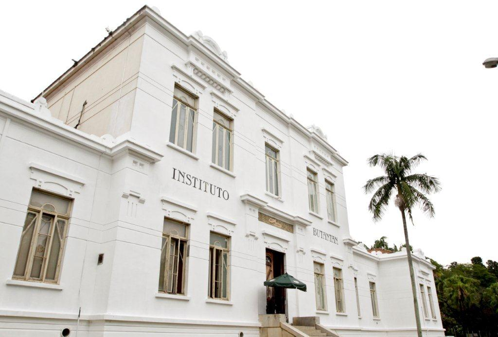 "All white facade of the building with 2 floors, the top one lower than the bottom. On the ground floor, 9 rectangular windows vertically. In the center small staircase and entrance door, with a green parasol. In front of the right end of the building, a palm tree high. To the side, garden with many green trees. On the upper floor, 5 rectangular windows vertically. Between the two floors, on the facade, is written ""INSTITUTO BUTANTAN""."