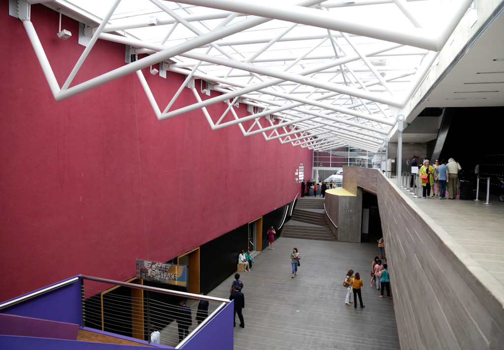 Inside photo of a large hall with 2 floors on the right side, where some people circulate. The central part has a single floor with a very high roof, formed by several white tubular structures side by side and semi transparent white cover through which the daylight passes. Gray concrete floor where several people circulate, with a staircase of 3 tosses of stylized shape in the background. To the right, on the ground level, black wall with 3 large pass doors. Above, on the level of the 2nd floor, large wall and quite fulfilled wine color.