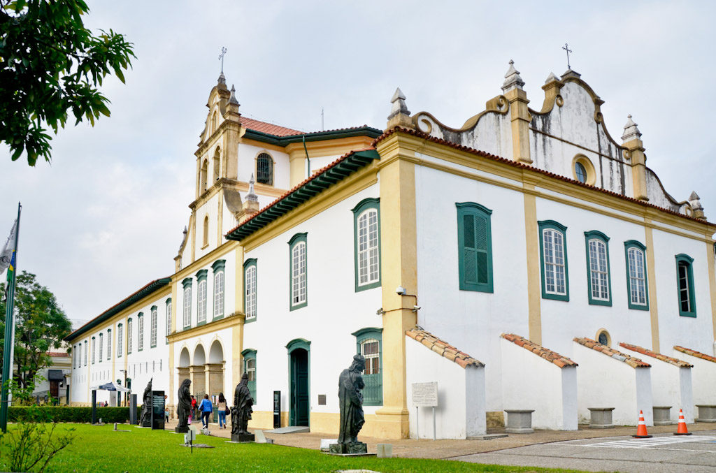 Diagonal picture of a baroque building with 4 floors. To the left, the entire front facade is white framed by beige bands. On the first floor, in the center, stands out three large entrance portals with the top in the shape of a semi-circle. On the 2nd floor, large row of several windows with dark green edges, from end to end. The 3rd and 4th floors rise only in the central part, forming the tower and church steeple, which has an iron cross at the top. To the right, the entire white facade framed by beige bands. On the 2nd floor, row of several windows with dark green edges, from end to end. On the ground level, on the left, a large, well-tended lawn with several sacred images in dark stone, measuring about 2.5 meters high.
